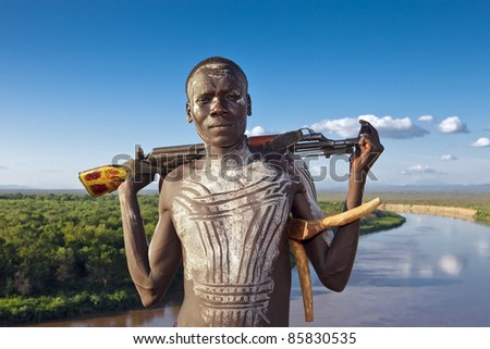 OMO VALLEY-AUG 13:Unidentified Karo Man with Omo River in the background Aug 13, 2011 in Omo Valley, Ethiopia.The ethnic groups in the Omo valley could disappear because of Gibe III hydroelectric dam. - stock photo