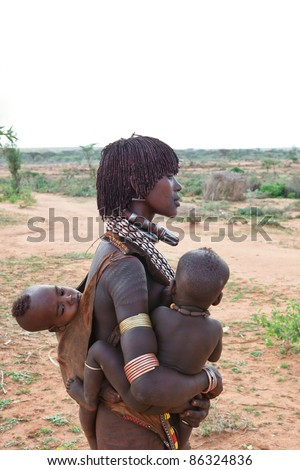 OMO VALLEY, ETHIOPIA - AUG 15: Unidentified Hamer woman with her children, the ethnic groups in the Omo valley could disappear because of Gibe III hydroelectric dam on Aug 15, 2011 in Omo Valley, Ethiopia. - stock photo