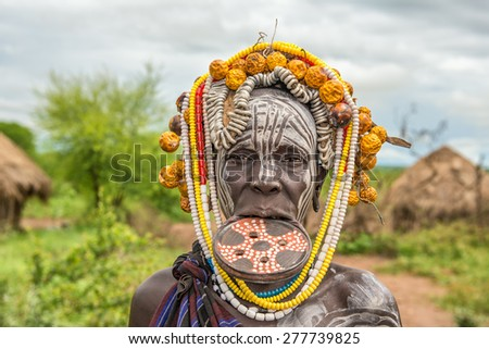 OMO VALLEY, ETHIOPIA - MAY 7, 2015 : Woman from the african tribe Mursi with big lip plate in her village. - stock photo