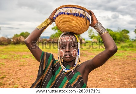 OMO VALLEY, ETHIOPIA - MAY 7, 2015 : Young boy from the African tribe Mursi with traditional jewelry in Mago National Park, Ethiopia. - stock photo