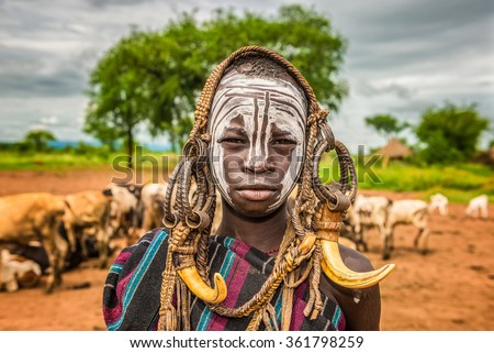 OMO VALLEY, ETHIOPIA - MAY 7, 2015 : Young boy from the African tribe Mursi with traditional horns in Mago National Park, Ethiopia. - stock photo