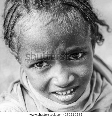OMO VALLEY, ETHIOPIA - SEPTEMBER 19, 2011: Unidentified Ethiopian girl in a yellow scarf looks uo in Ethiopia, Sep.19, 2011. People in Ethiopia suffer of poverty due to the unstable situation