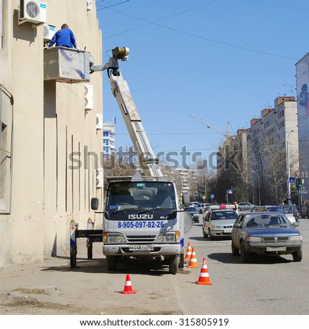 OMSK, RUSSIA - APRIL 22, 2010: Team of workers mounts air conditioning on outside wall of house - stock photo