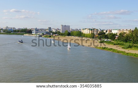 OMSK, RUSSIA - August 15, 2009: summer top view of Irtysh river with sailing ships, beach and panorama of city