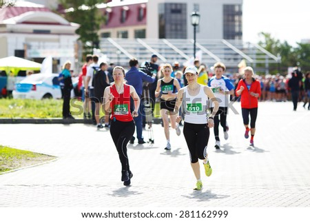 OMSK, RUSSIA - MAY 24 : A group of unidentified marathon runners compete at the Spring Half Marathon 2015 in Omsk, Russia, May 24,  2015. - stock photo