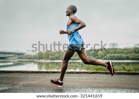 Omsk, Russia -  September 20, 2015: young runner Kenyan John Kyui runs along river during Siberian international marathon - stock photo