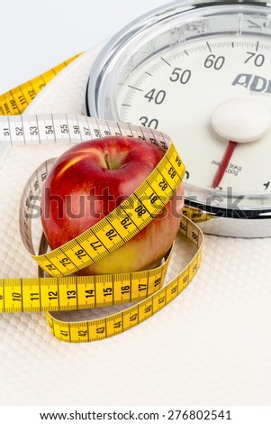 on a bathroom scale is an apple. symbolic photo for slimming and healthy, vitamin-rich diet. - stock photo