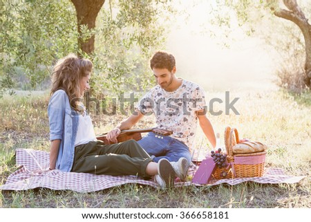 On a beautiful sunny day, a couple of young lovers, makes picnic on grass among olive groves in Tuscany, Italy. Man leans on guitar while talking with his girlfriend - stock photo