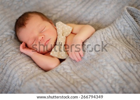 on a bed in a knitted blanket sleeping baby - stock photo