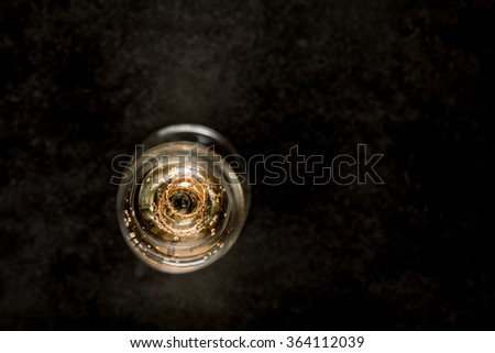 on a black background wedding rings in a glass of champagne - stock photo