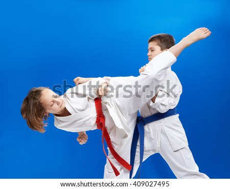 On a blue background boy and girl are hitting karate punches - stock photo