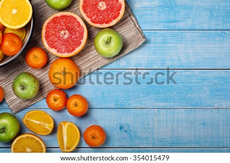 On a blue wooden table variety of fruits - grapefruit, tangerines, apples and oranges. Top view. Mixed fruits background.  - stock photo