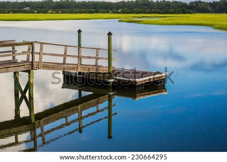 On a calm morning, a boat dock reflects in the blue waters of an inlet along the Atlantic Coast - stock photo