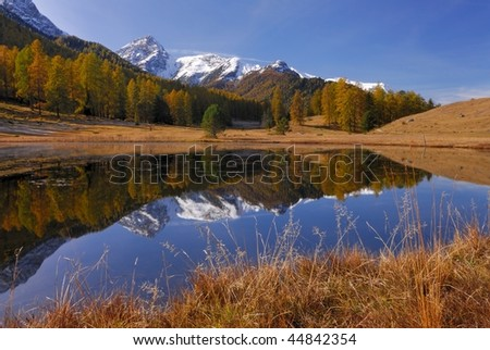 On a clear day in autumn a snow mountain is reflected in a little lake in the Swiss Alps. - stock photo