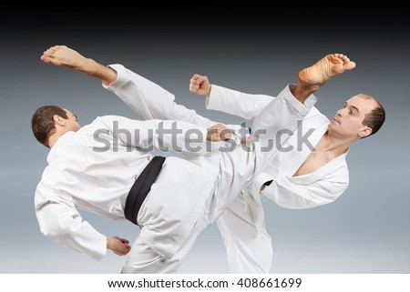 On a dark background a kick in the performance of an athlete with a collage of black belt