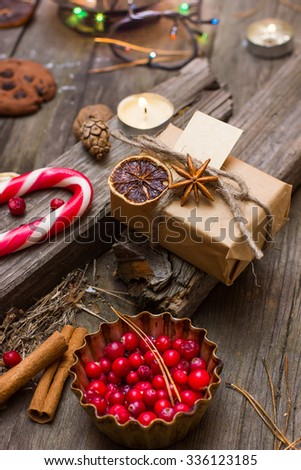 on a dark wooden table lie candles, cookies, candy, berries, garlands, cones. Christmas concept