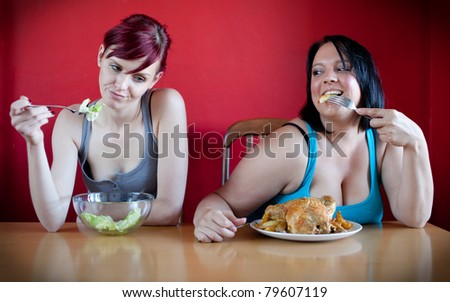 On a diet. Skinny woman eating a few leaves of salad while the overweight woman is eating whole chicken. - stock photo