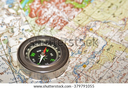 On a few maps is the magnetic compass. Compass laying on a topographic map. - stock photo