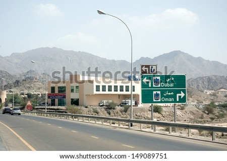 On a freeway, a sign indicates Dubai and Oman. A pharmacy, with trucks on its parking, stands close to the road. There are some cars on the road and arid mountains are visible in the background. - stock photo