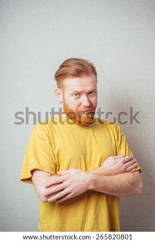 on a gray background man with a beard in a yellow shirt folded hands - stock photo