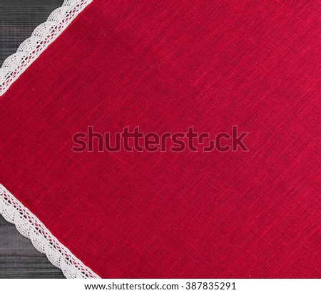 On a gray background of wooden red cloth with white linen woven handmade lace - stock photo