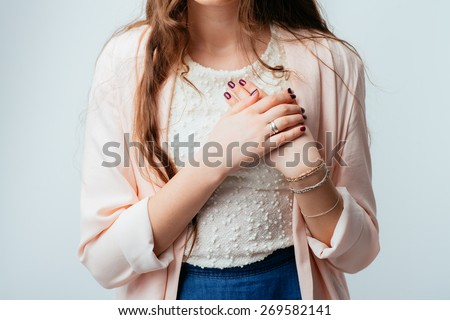on a gray background young girl at heart aches - stock photo