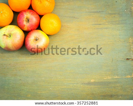 On a green wooden old table variety of fruits  - mandarins, apples . Top view. Mixed fruits background. - stock photo