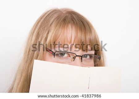 On a light background the girl in eyeglasses hides behind the book