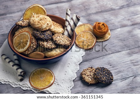 On a light wooden background blue ceramic bowl with cookies, decorated with a dried orange slices, rose from the orange peel, chocolate rolls, white napkin with lace