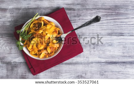 On a light wooden background in vintage style food dinner plate with Bolognese Tagliatelle pasta, fork, napkin, towel red, green curly parsley - stock photo