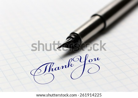 "On a piece of the cell shows ""thank you"" and a pen"