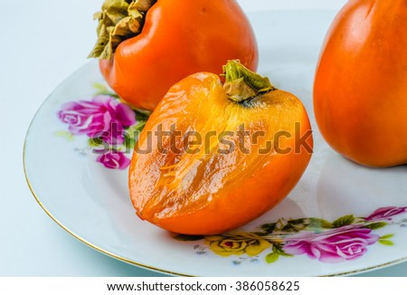 On a plate persimmon fruit lie. Two whole and half.