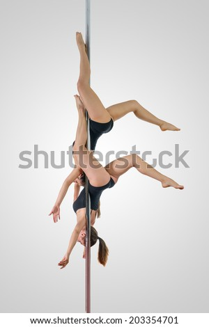 On a pole. Two young sporty girls in dangerous acrobatic position on a pole