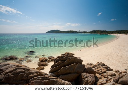 On a rocky cliff looking down at the perfect white sand beach and gorgeous blue turquoise water of island paradise, Koh Lipe (aka Ko Lipeh) in Thailand. - stock photo