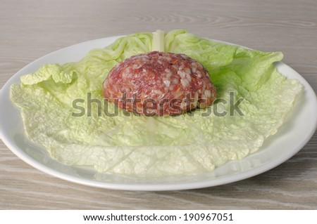 On a sheet of savoy cabbage  portion raw ground beef