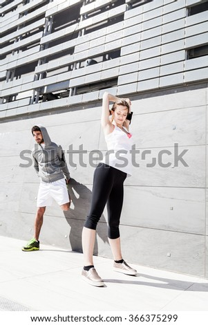 On a sunny day, a couple of friends, man and woman, in sportswear does stretching outdoors near a building  - stock photo