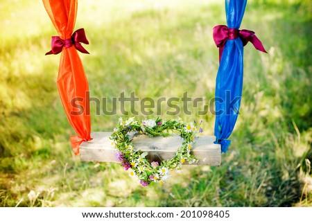 on a swing wreath of flowers. heart - stock photo