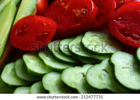 on a table stacked slices fresh cucumbers and tomatoes