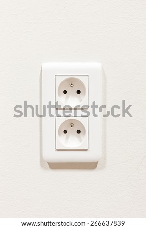 on a white wall, there is a socket with two outlets - stock photo
