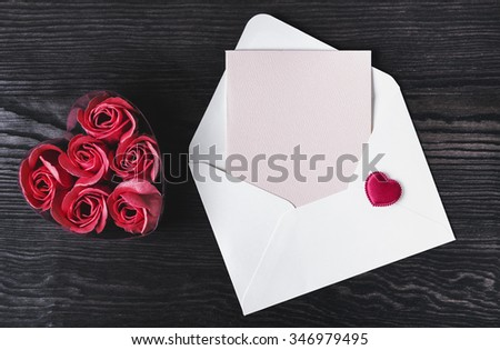 On a white wooden table composition for Valentine's Day, heart tissue in an envelope, a letter, a pen, there is a blank space for text greetings - stock photo