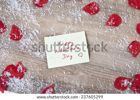 on a wooden background a yellow Sticky note with text happy valentines day. Decorated with snow and red blossoms - stock photo
