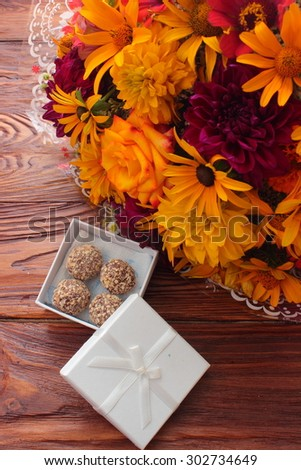 on a wooden board are candy and flowers