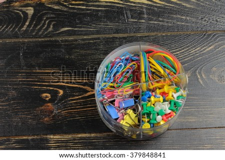 on a wooden board in a plastic box are rubber bands, paper clips, binders, buttons cloves - stock photo