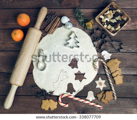 On a wooden desk background Christmas composition - candy cane, dough figurines, tree branch balls, raisins, nuts, cinnamon sticks, cookies, anise, mandarins; bump; roll out the dough layer; plunger - stock photo