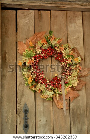 on a wooden door weighs a wreath of yellow autumn leaves and red berries