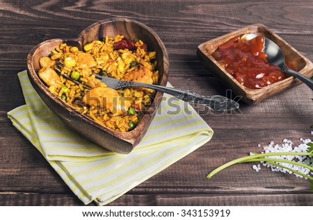On a wooden table dinner - delicious food in plate of paella in the form of heart, sweet and sour vegetable tomato red sauce, fork, spoon, cotton cloth, green celery and thyme, sprinkled coarse salt - stock photo
