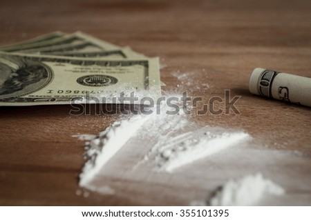 on a wooden table scattered white powder near the money one bill rolled into a tube - stock photo