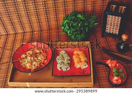 On a wooden tray, there are two red plates on a single two servings of sushi with salmon and Philadelphia cheese with smoked eel and the second plate udon noodles with  peppers onion and shrimp sauce - stock photo