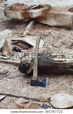 On a workplace near a log among sawdust and tree scraps there is an axe.