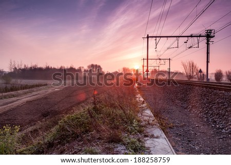 on an early morning at sunrise right next to a railway line with fog banks in the distance - stock photo